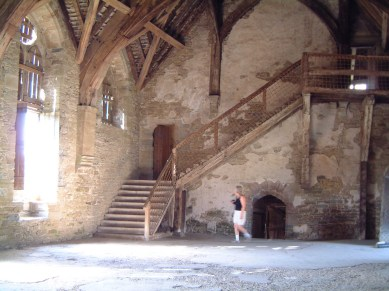 Large stone room with wooden beams and staircase