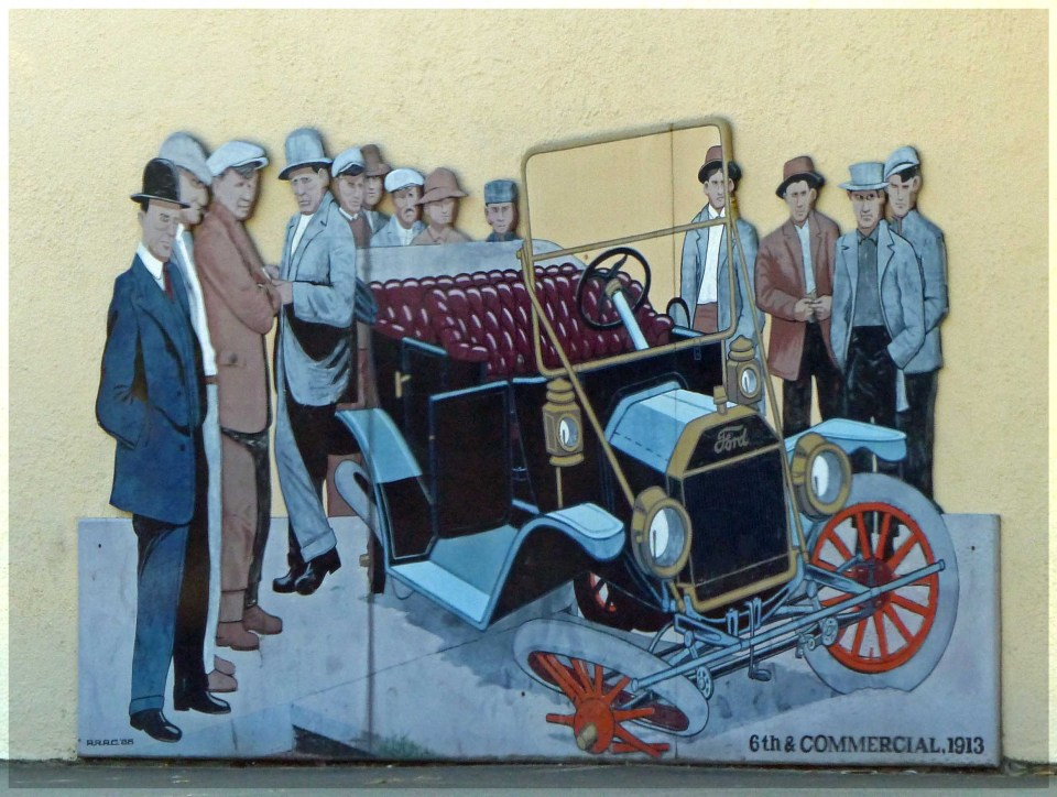 Mural of old car and lots of men standing around
