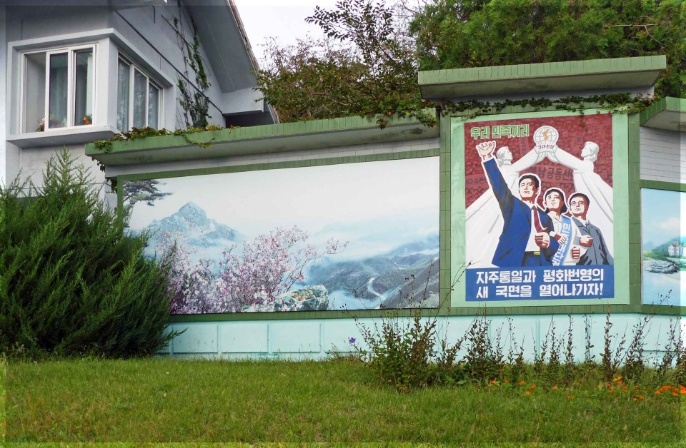 Large poster depicting people in front of white statues