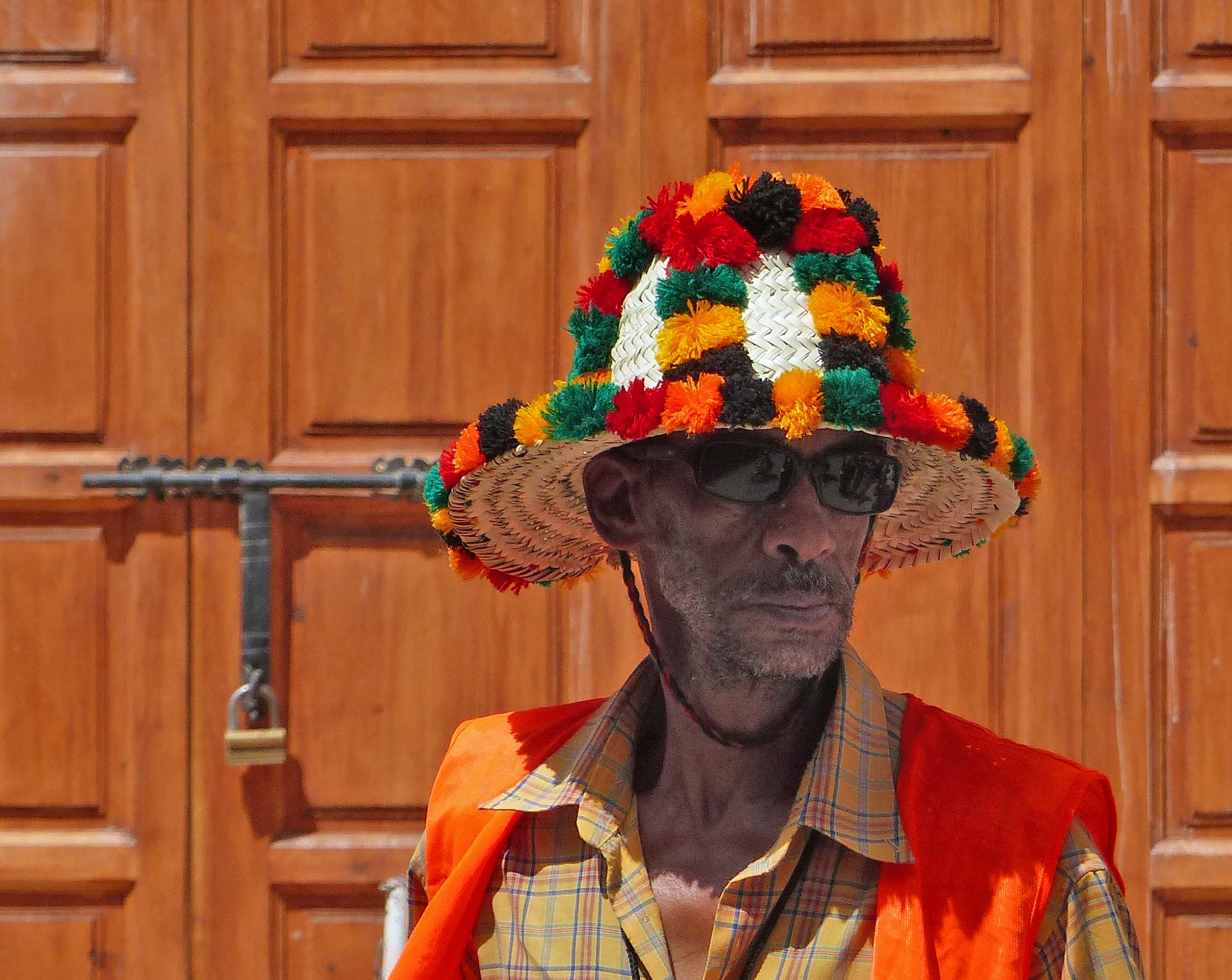 Man in straw hat decorated with pompoms