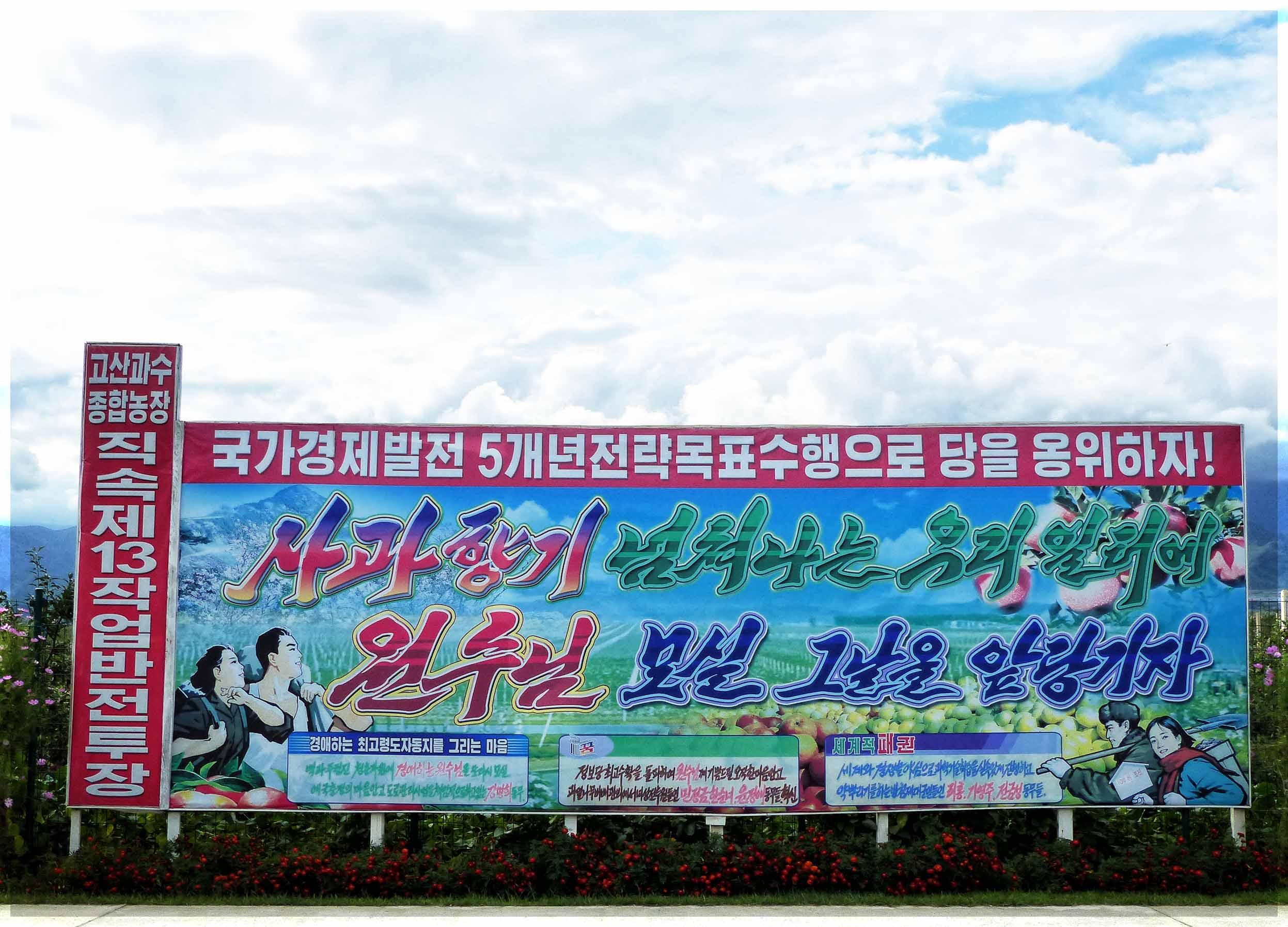 Large poster depicting rural scene with Korean slogans