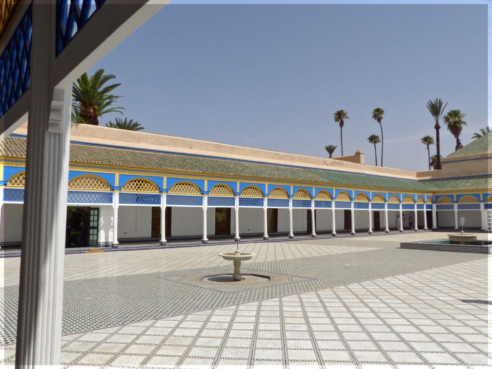 Large white courtyard with portico painted in blue and yellow