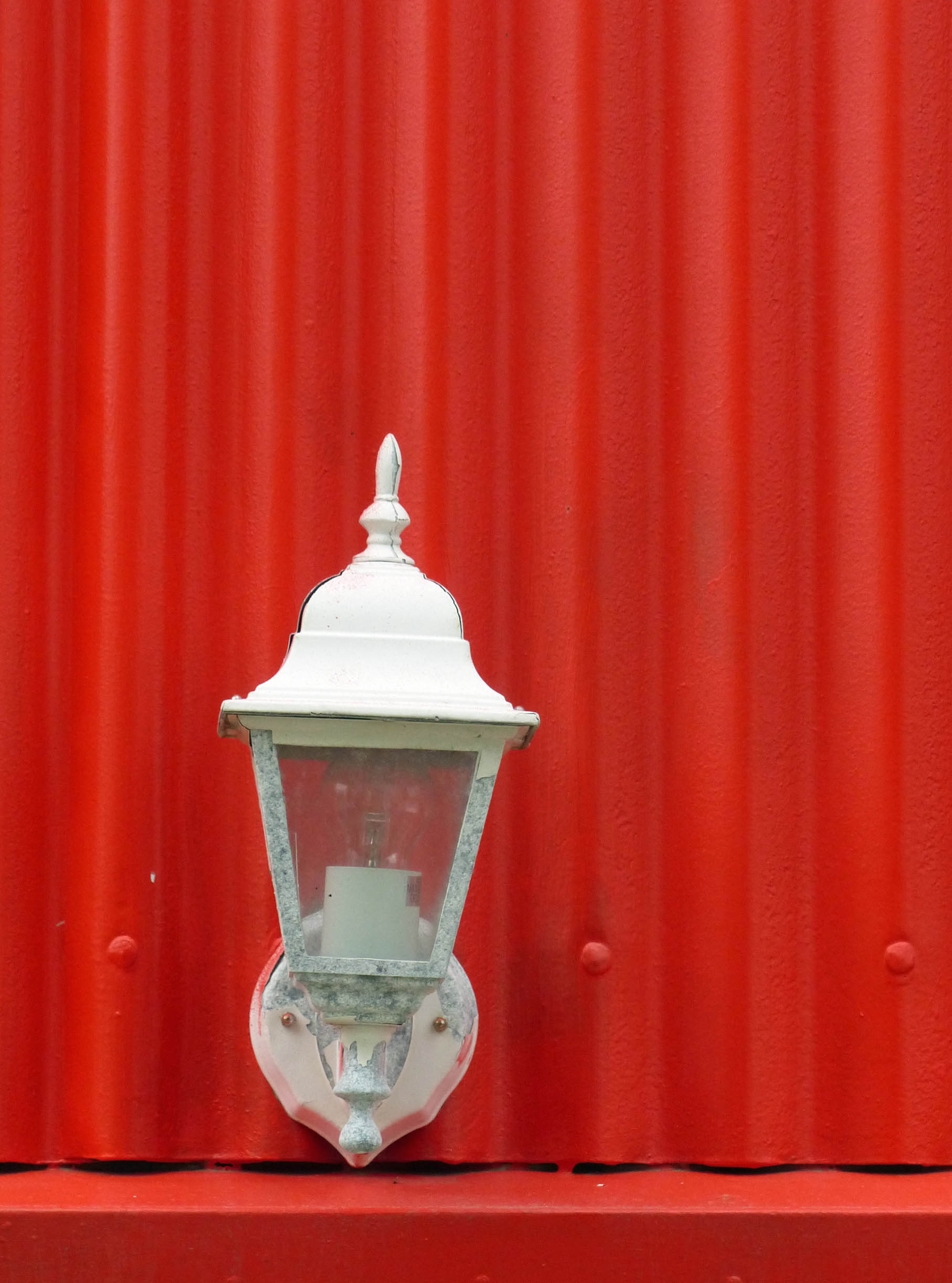 Red wall with small white wall lamp