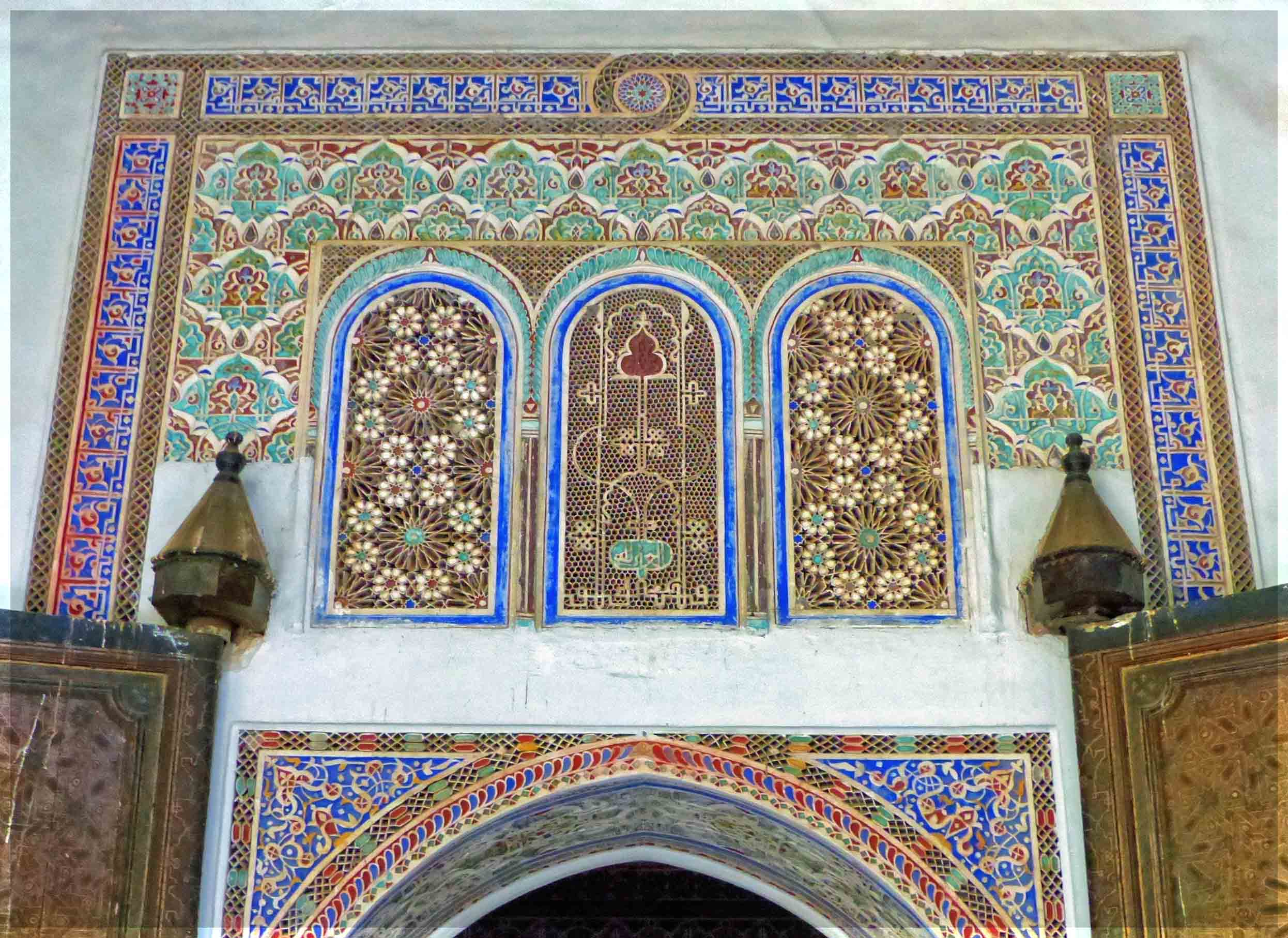 Decorative tiles in blue and green above an arched door