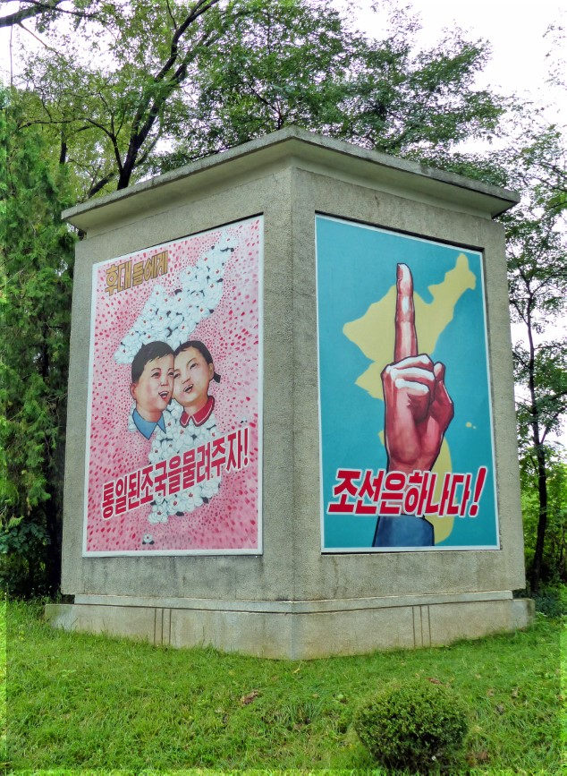 Two large posters, one of two children, other of hand with one finger raised