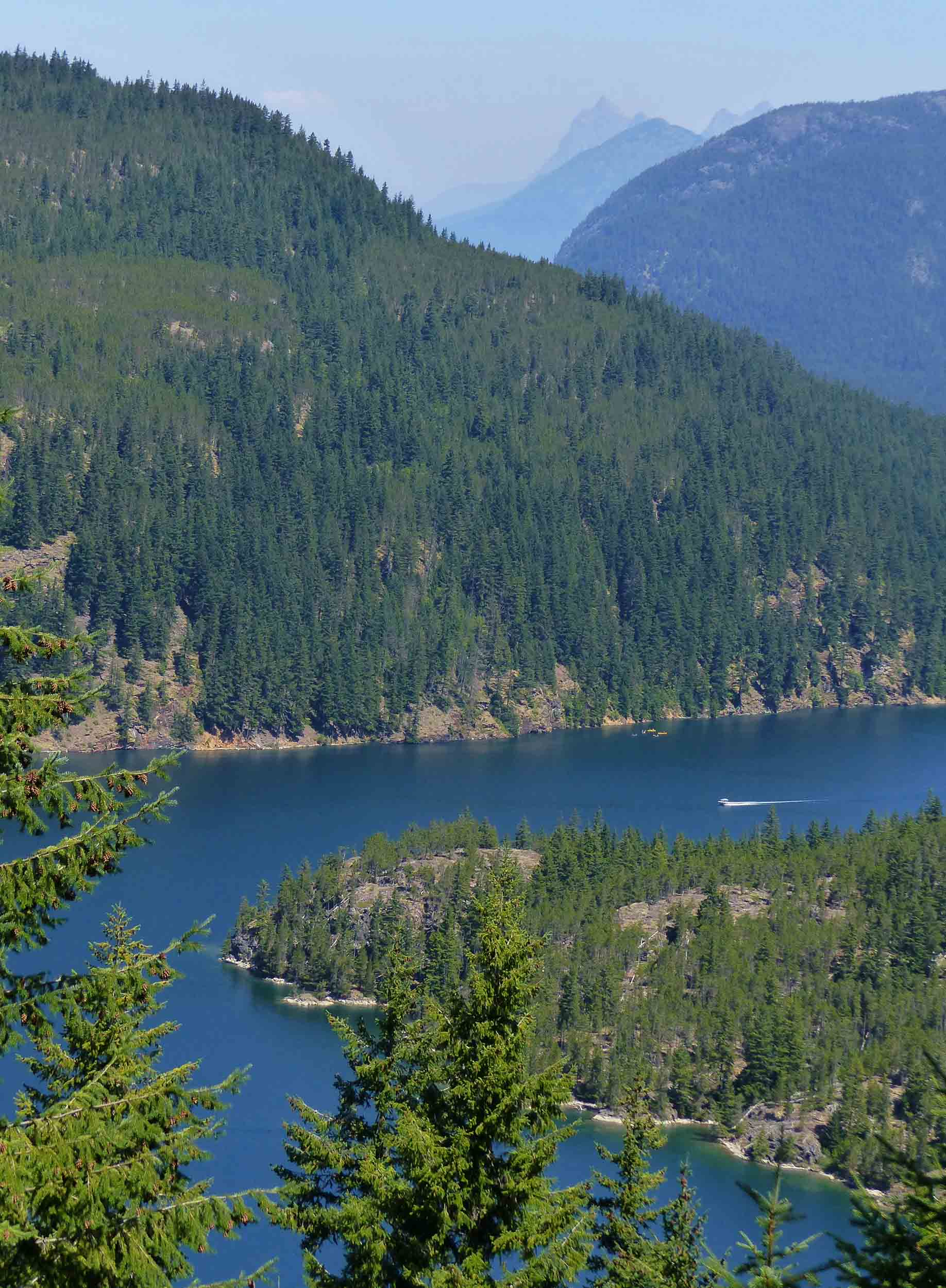 Looking down at deep blue lake among pine covered mountains