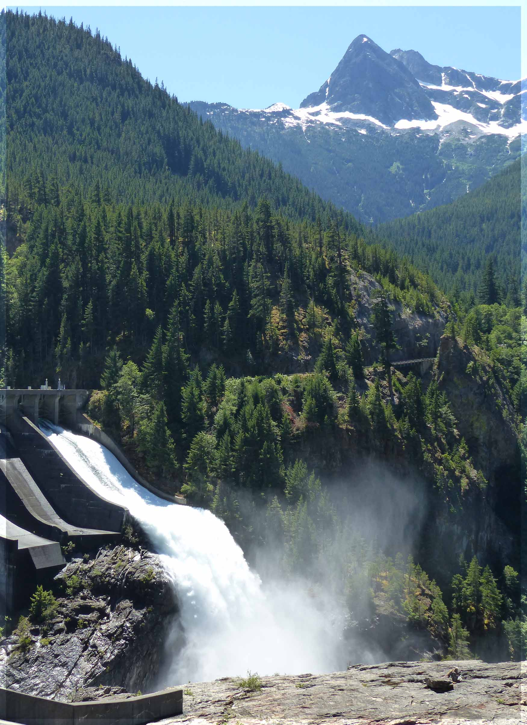 Water pouring from dam with pine covered mountains behind