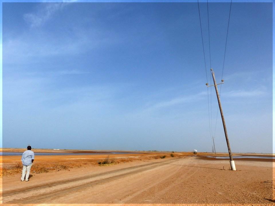 Sandy desert road with man standing