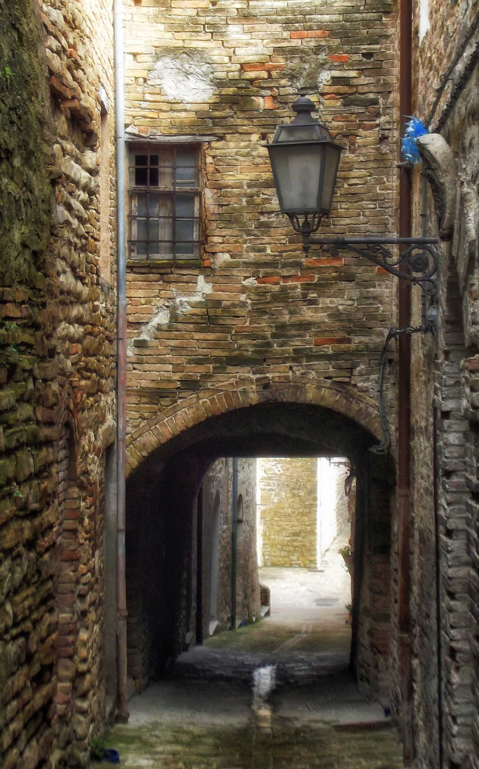 Arched passageway under a stone house