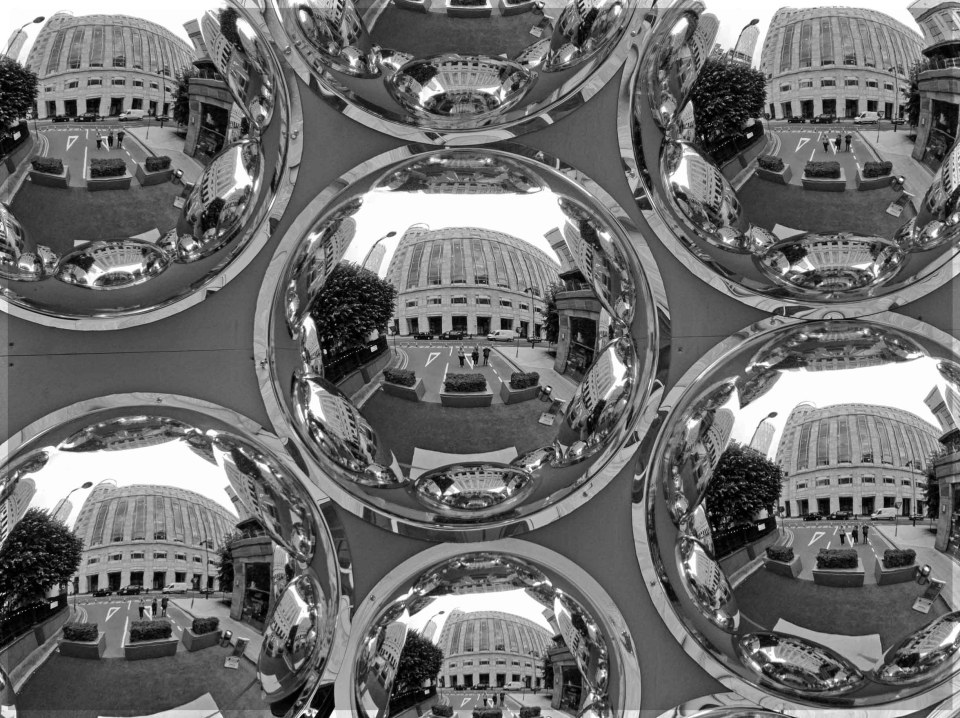 Set of round mirrors reflecting people and buildings