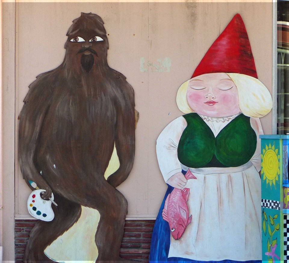 Mural of hairy figure and woman in conical red hat