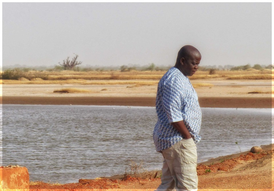 African man standing by small pool surrounded by sand