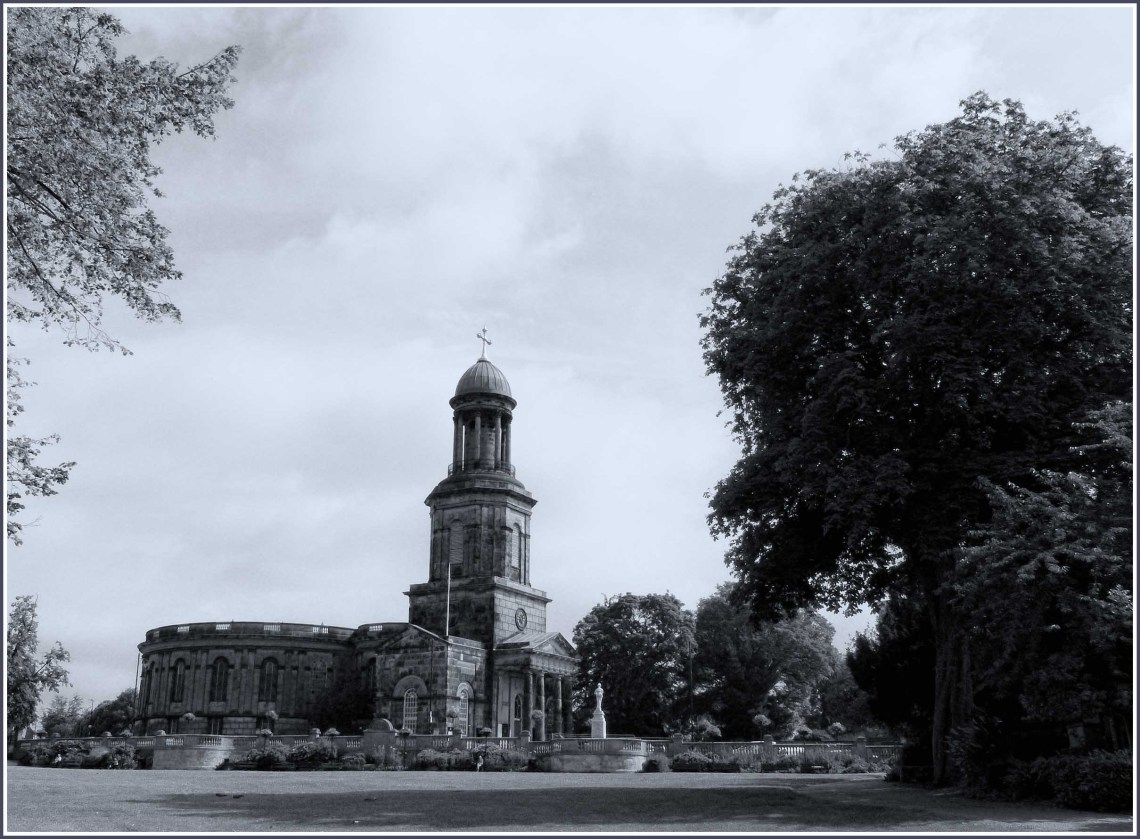 Black and white photo of a church with a park in front
