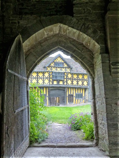 Yellow half-timbered building seen through a large heavy door