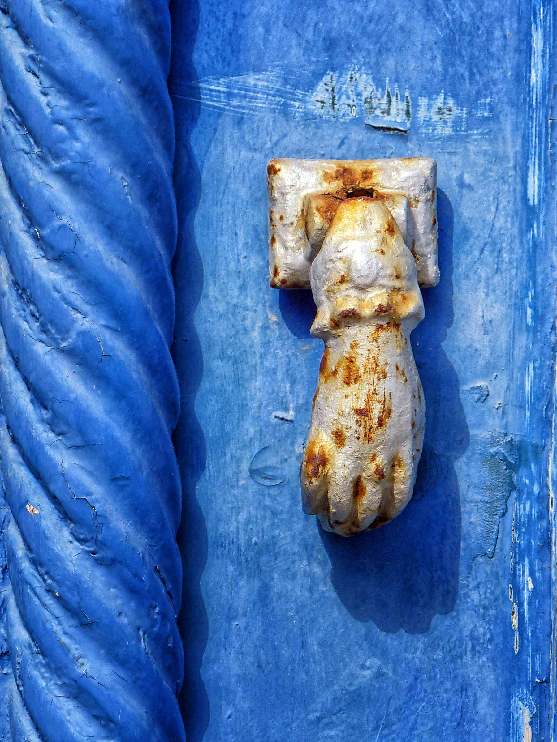 Detail of blue painted door with hand-shaped knocker