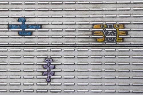 Three tiny multi-coloured paintings on ridged metal surface