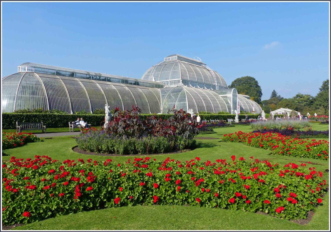 Large glass conservatory with lawns and flower beds