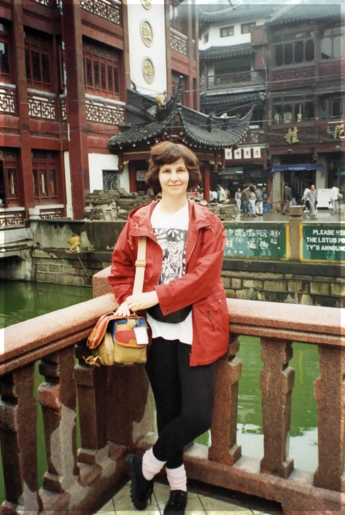 Woman standing in front of traditional Chinese buildings