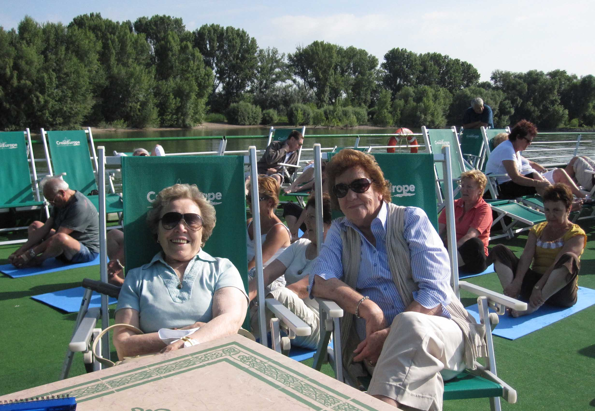 Two ladies in deck chairs on a boat on a river