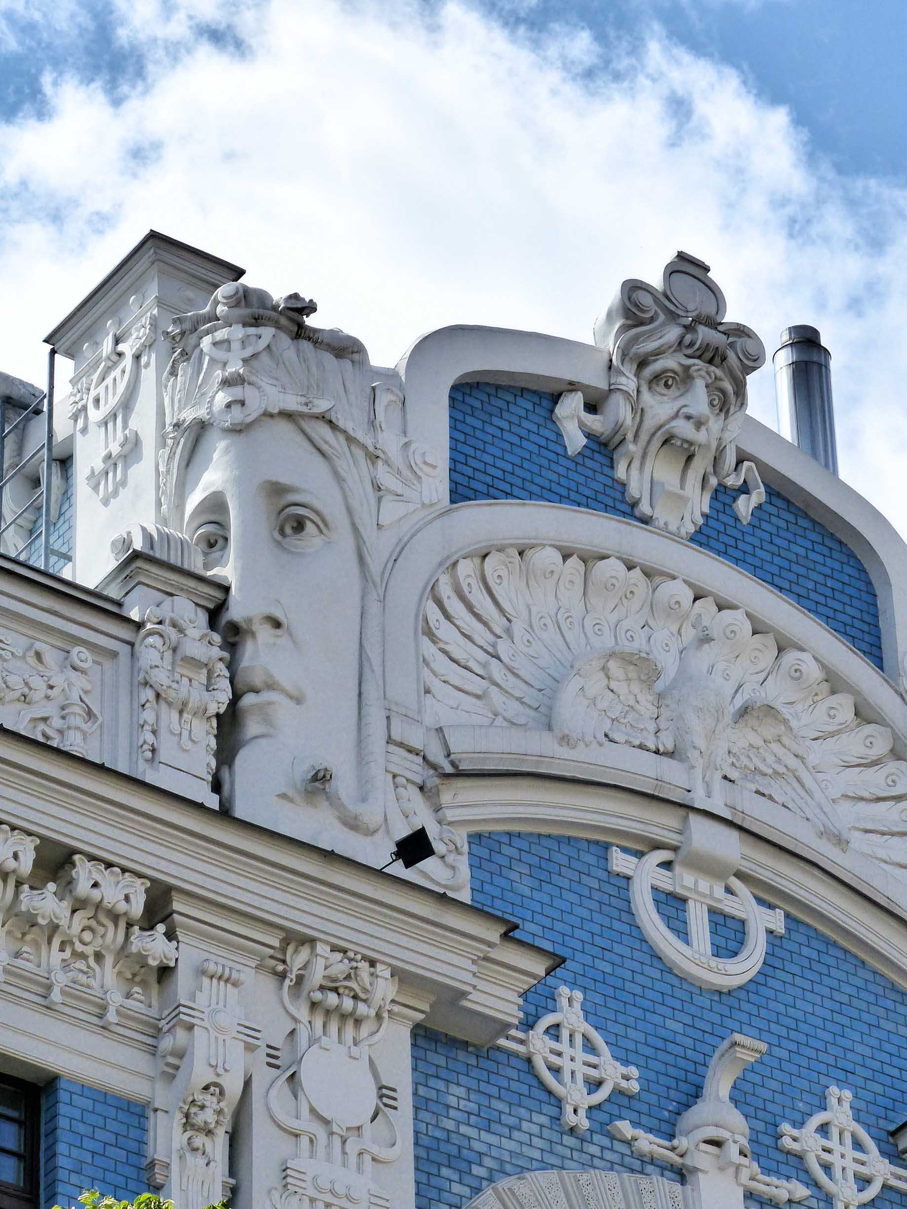 Ornate blue building with large female face and other details carved in white stone