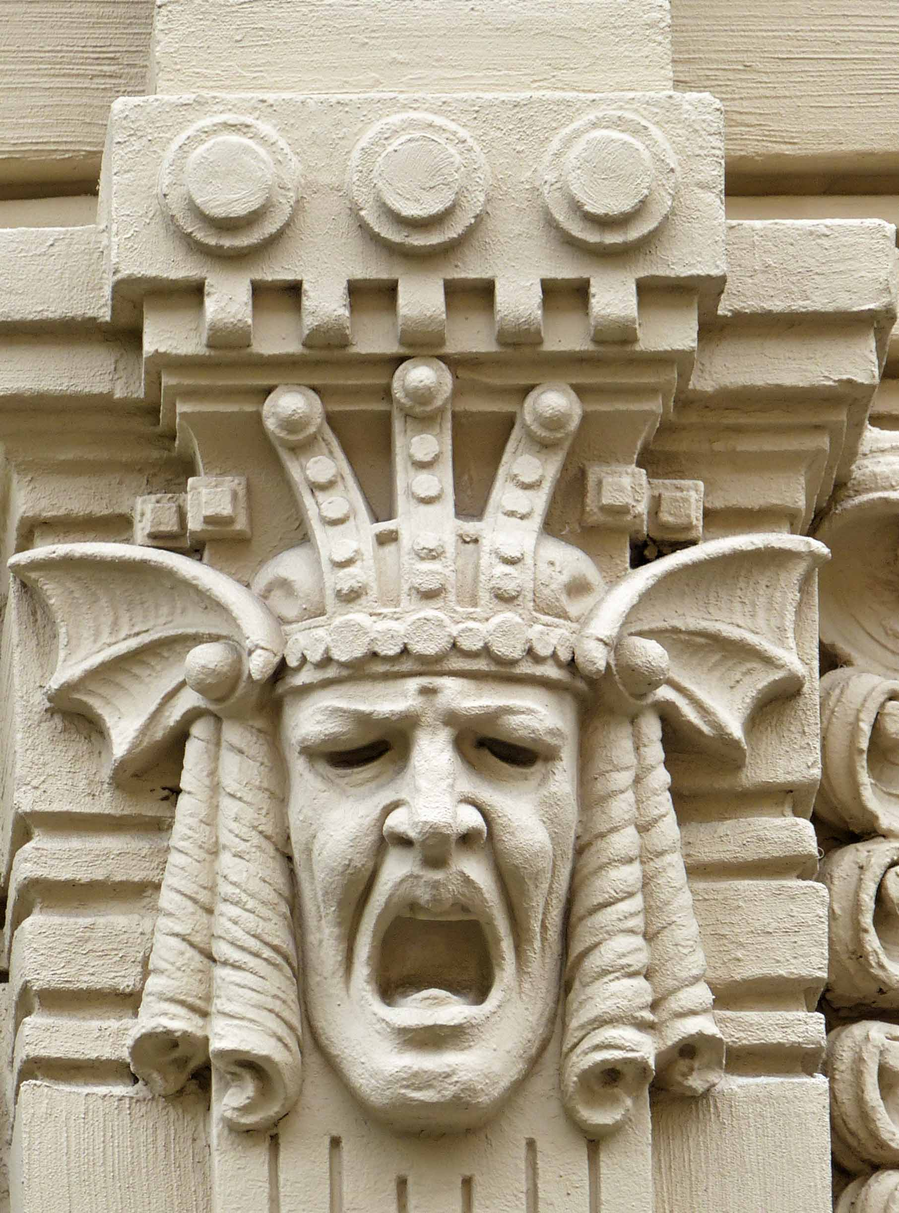 Fierce face with headdress carved in stone