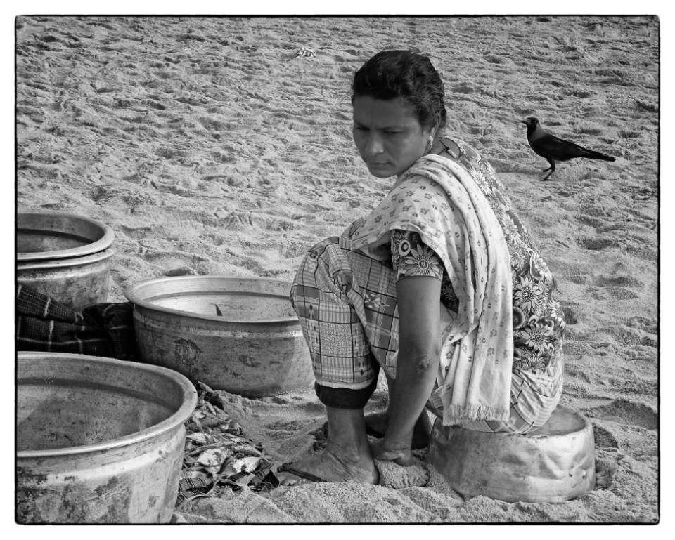 Black and white photo of lady cleaning fish on a beach