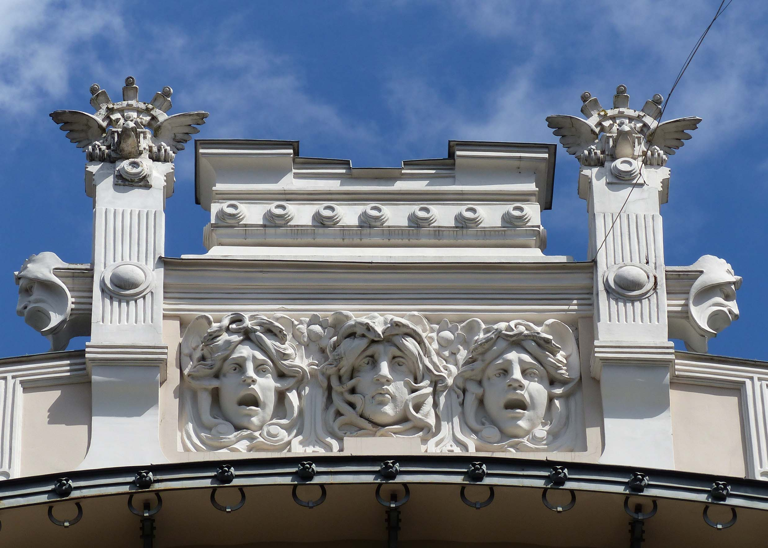 Carving of three faces at the top of a building