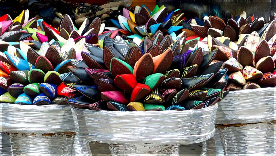 Colourful shoes piled into silver baskets