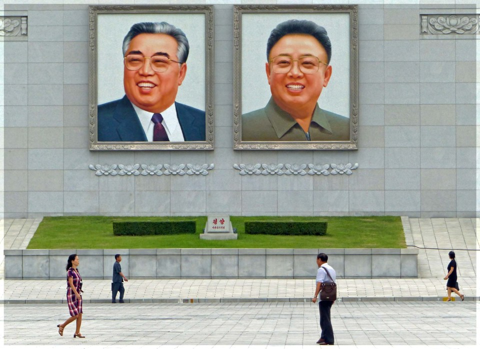People walking past two large portraits of smiling men