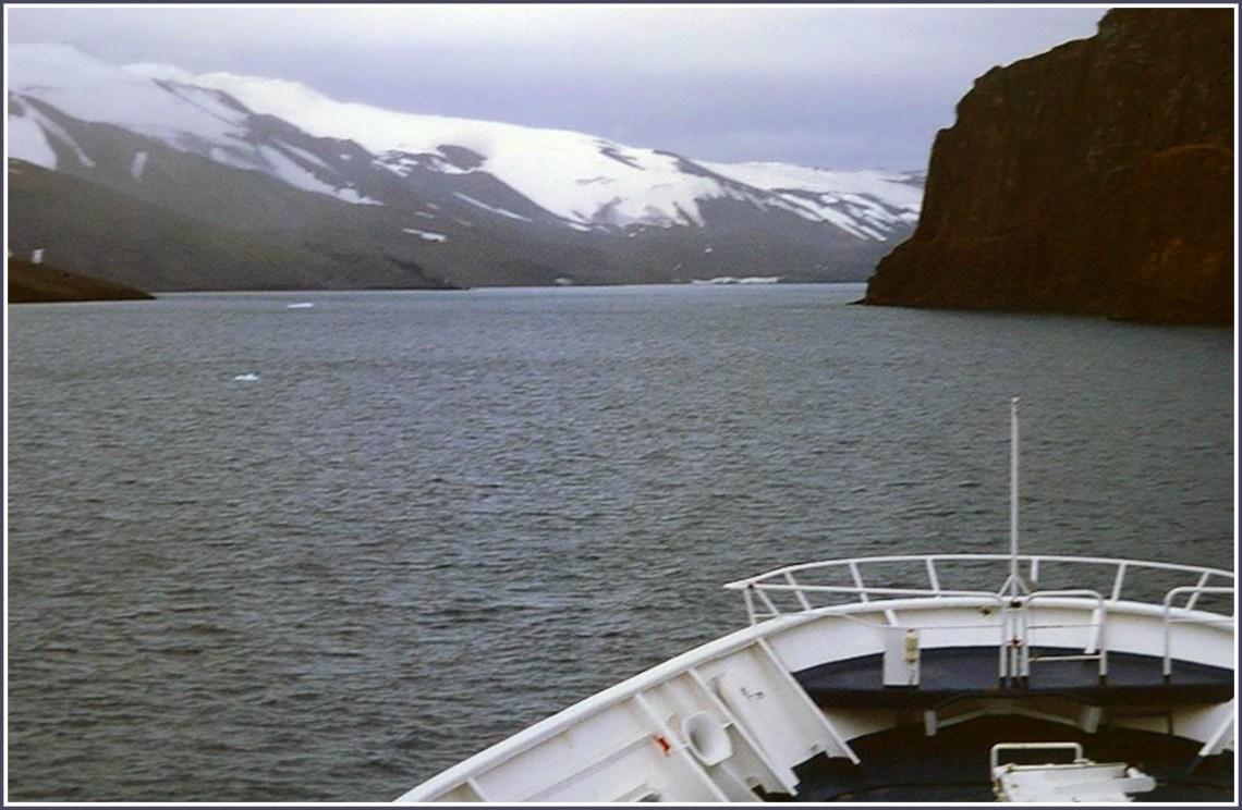 Bow of ship sailing towards snowy coastline