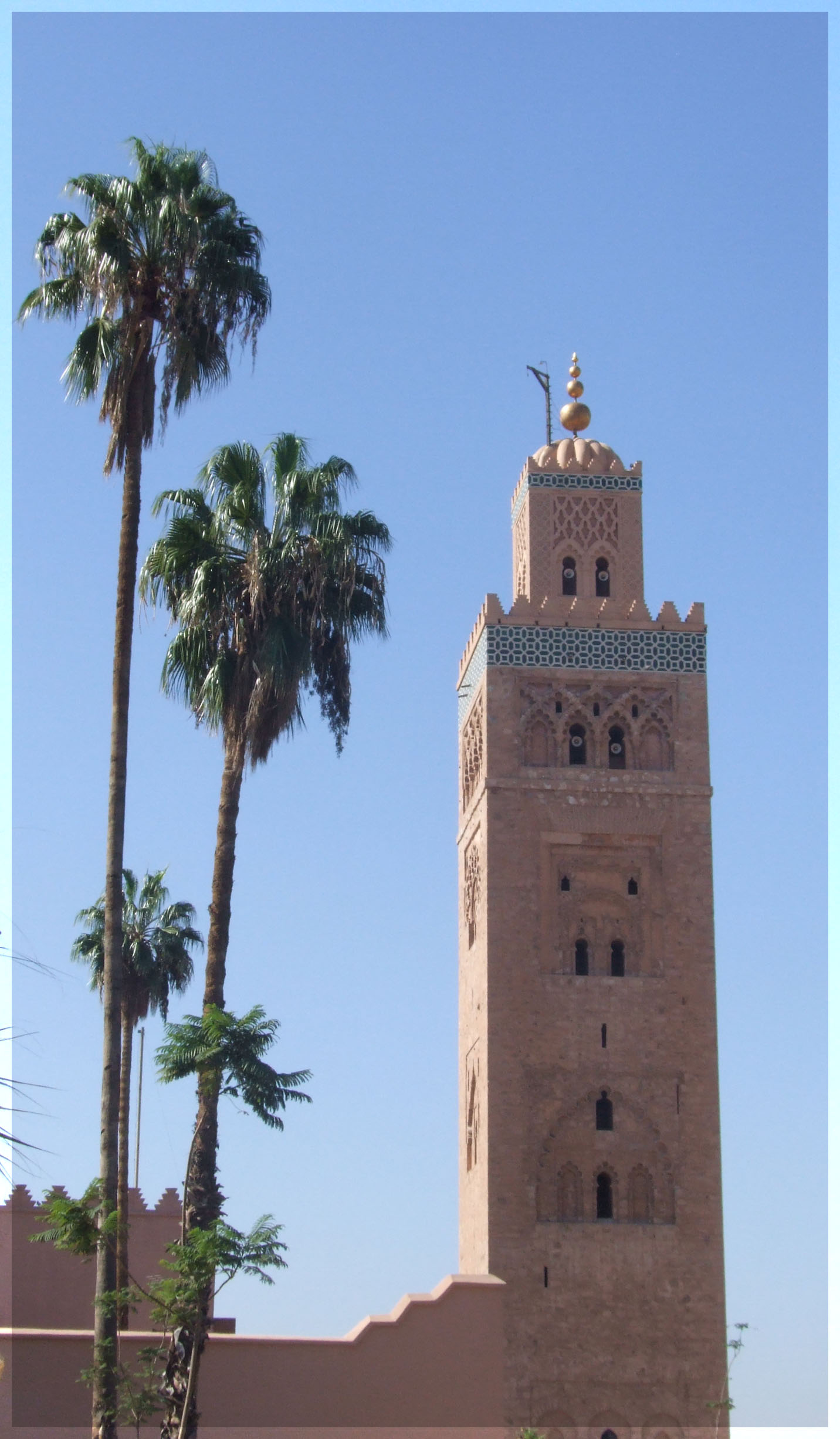 Tall square minaret and palm trees