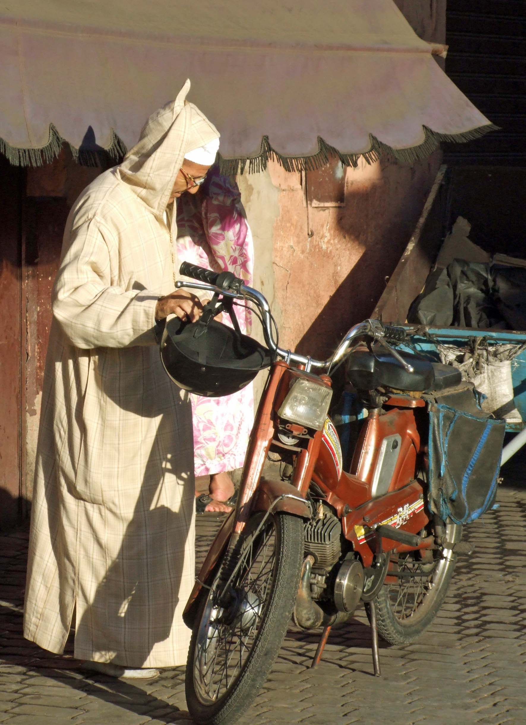Man in traditional Arab robe with bicycle