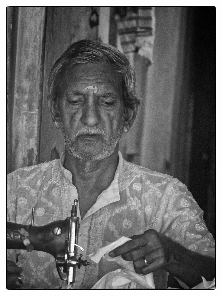 Black and white photo of a man sewing