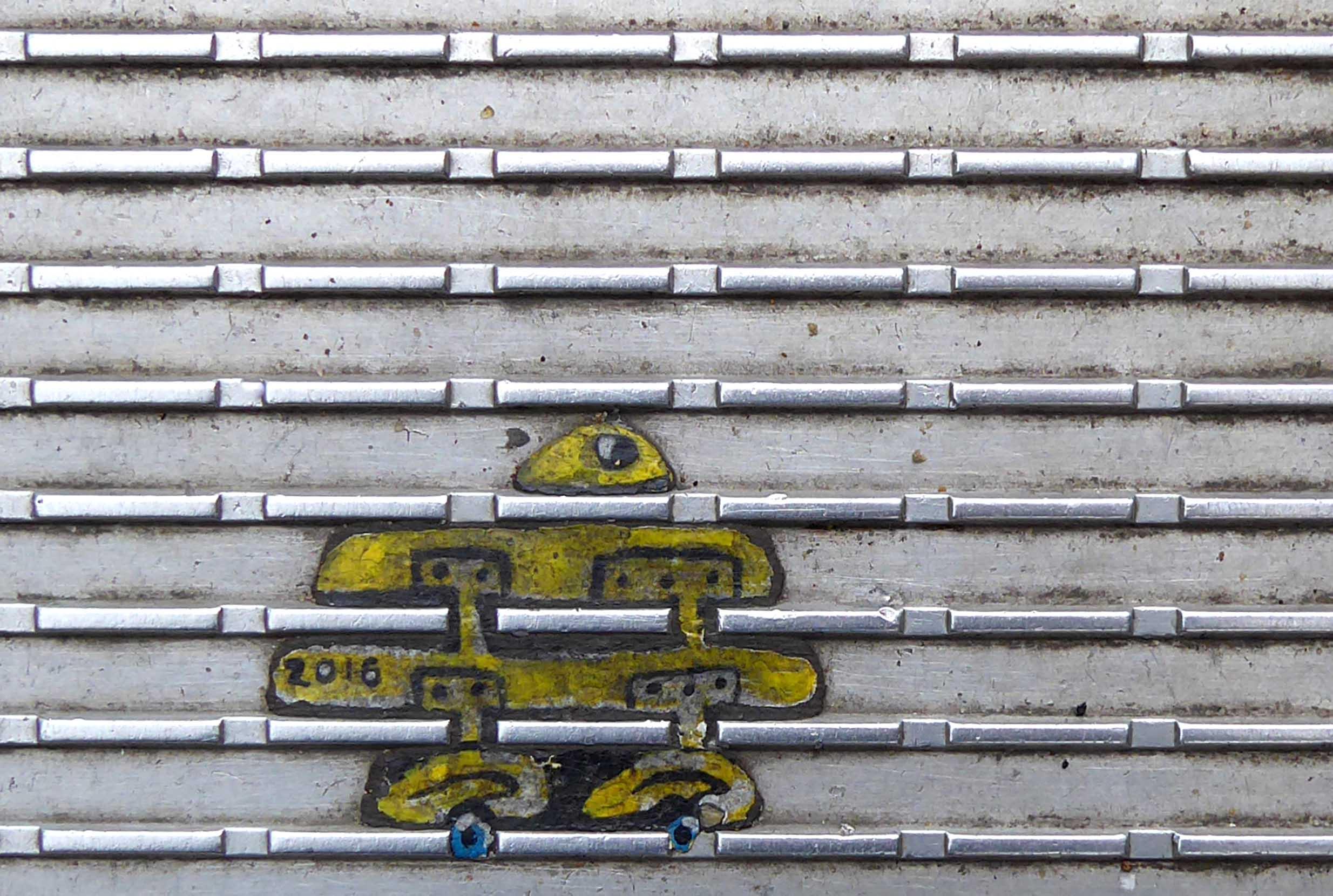 Tiny yellow painting on ridged metal surface