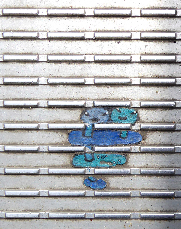 Tiny blue painting on ridged metal surface