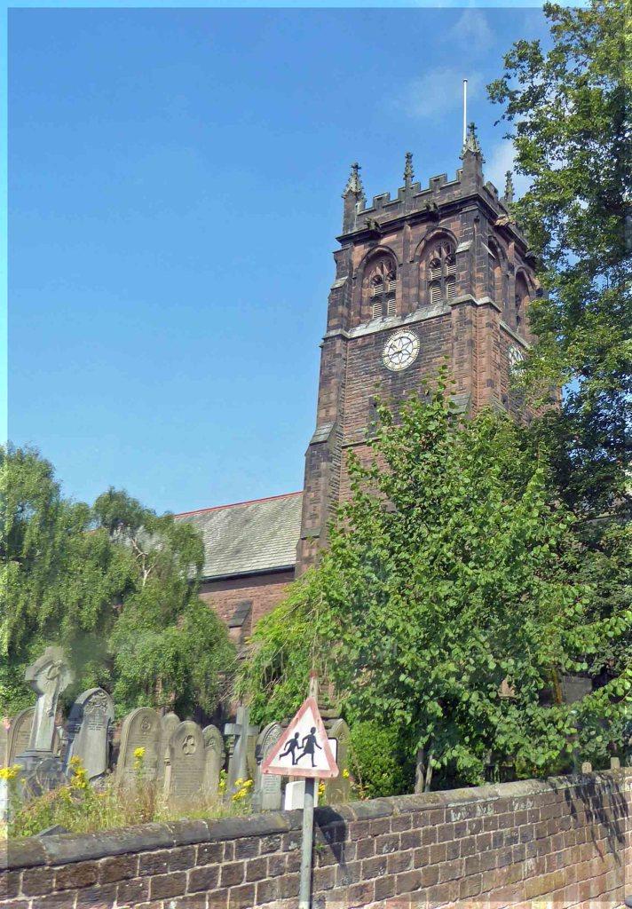 Church tower seen over brick wall