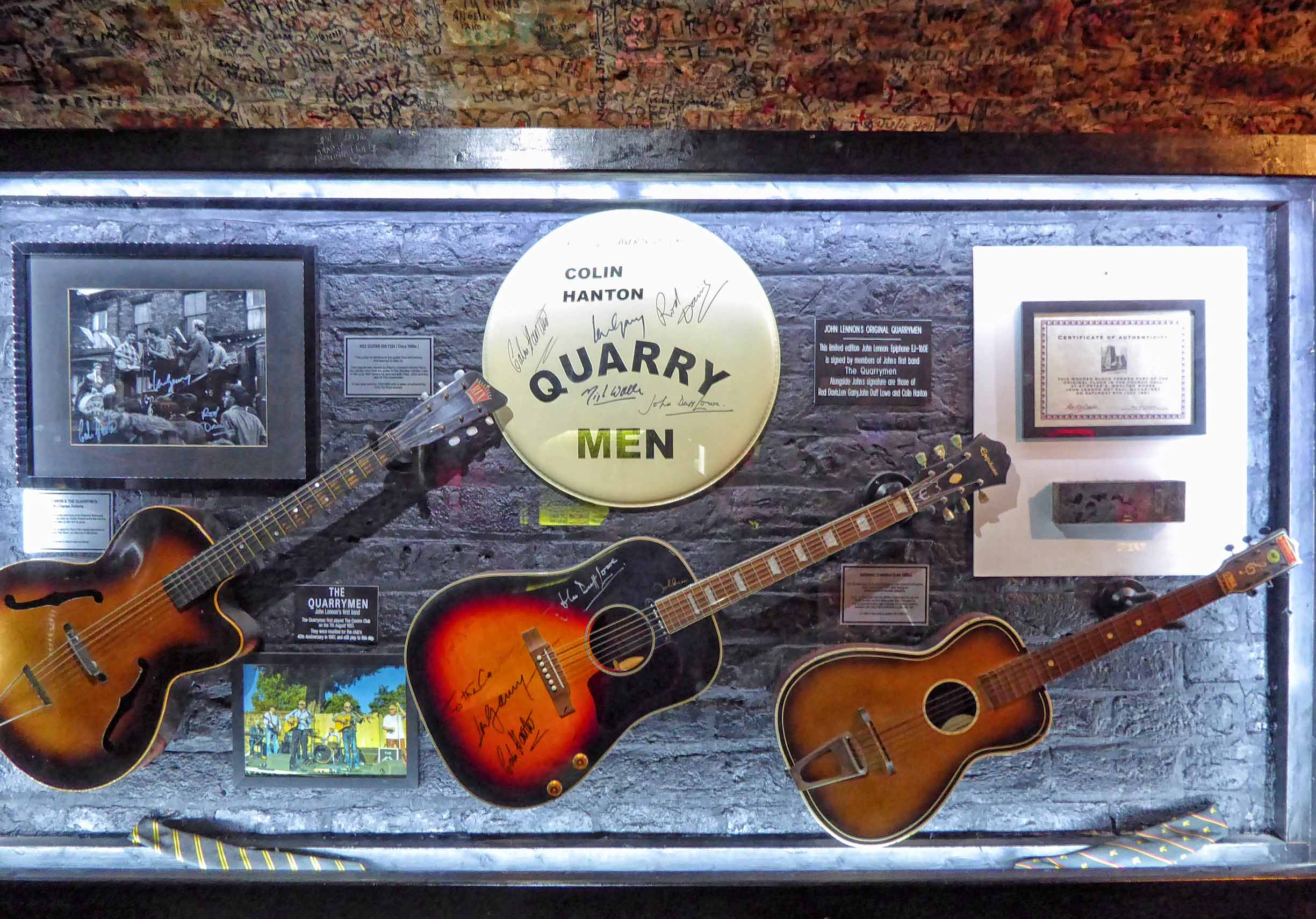 Display case with guitars and old photos