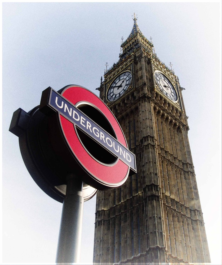 Tall clock tower and London Underground sign