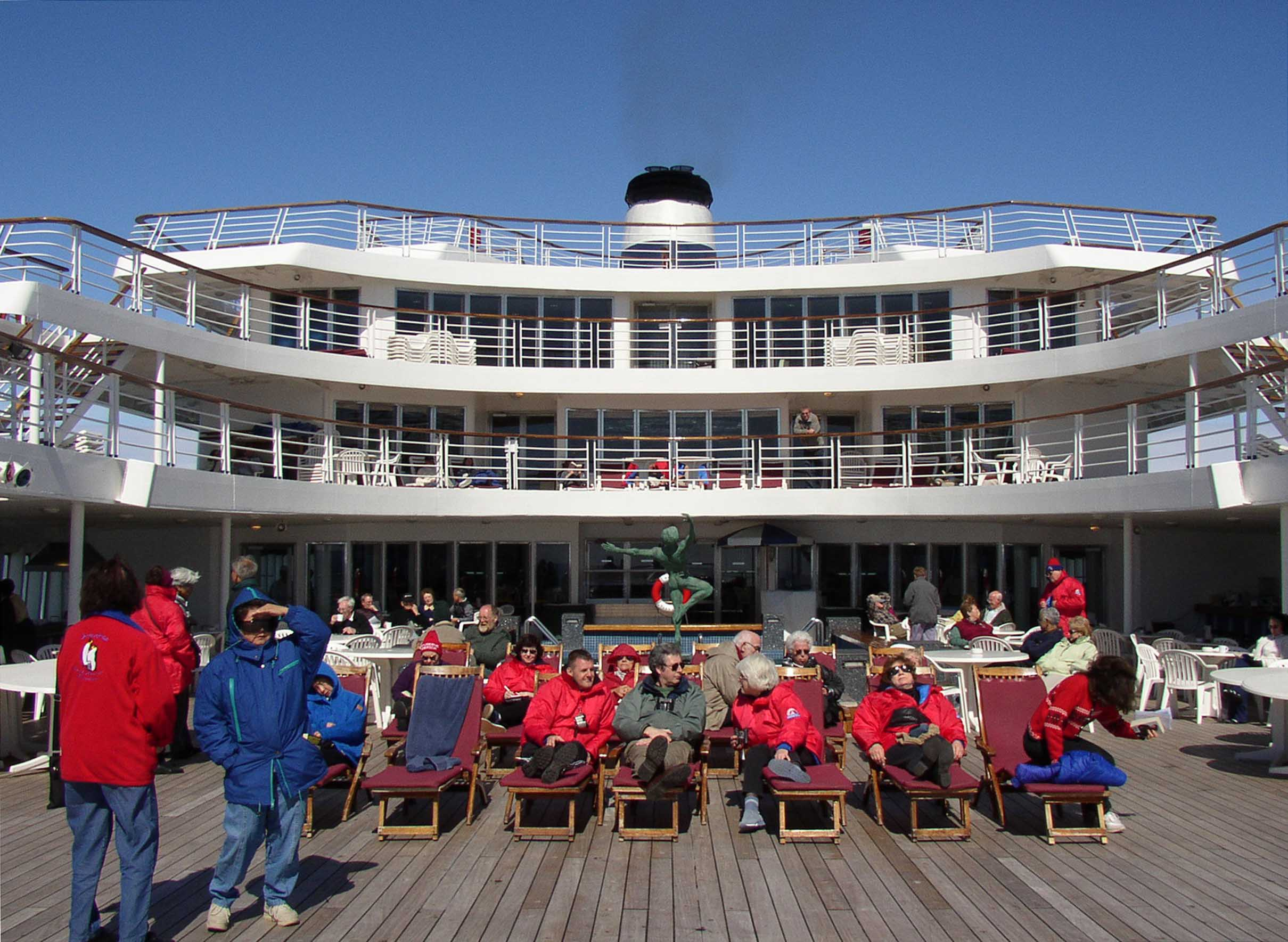 People relaxing on loungers on a ship, wearing warm clothes