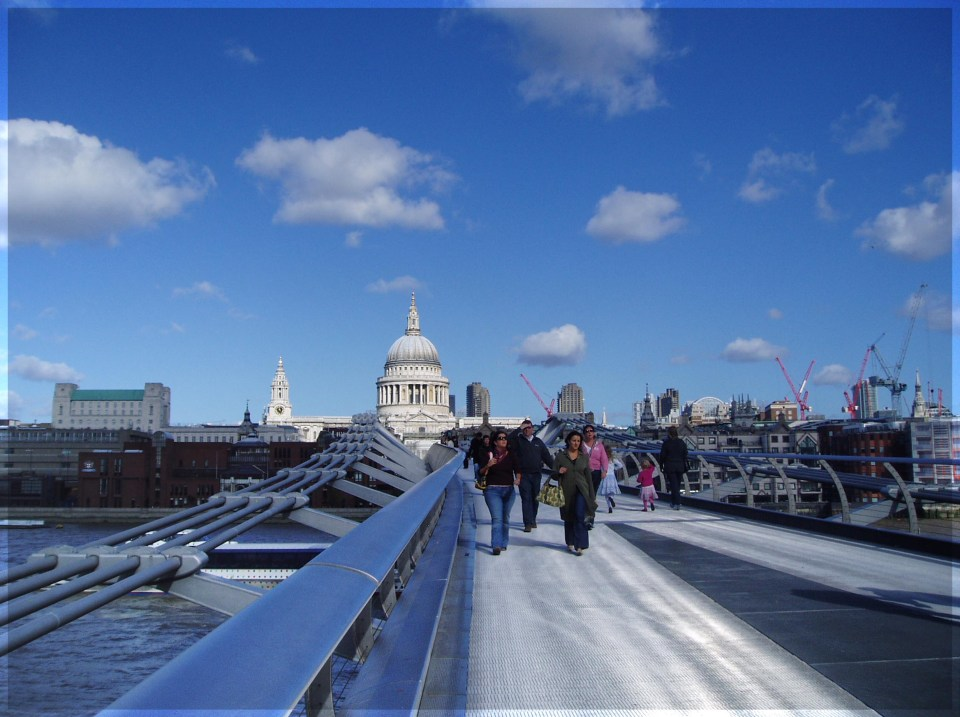 People walking across a bridge with a city skyline beyond