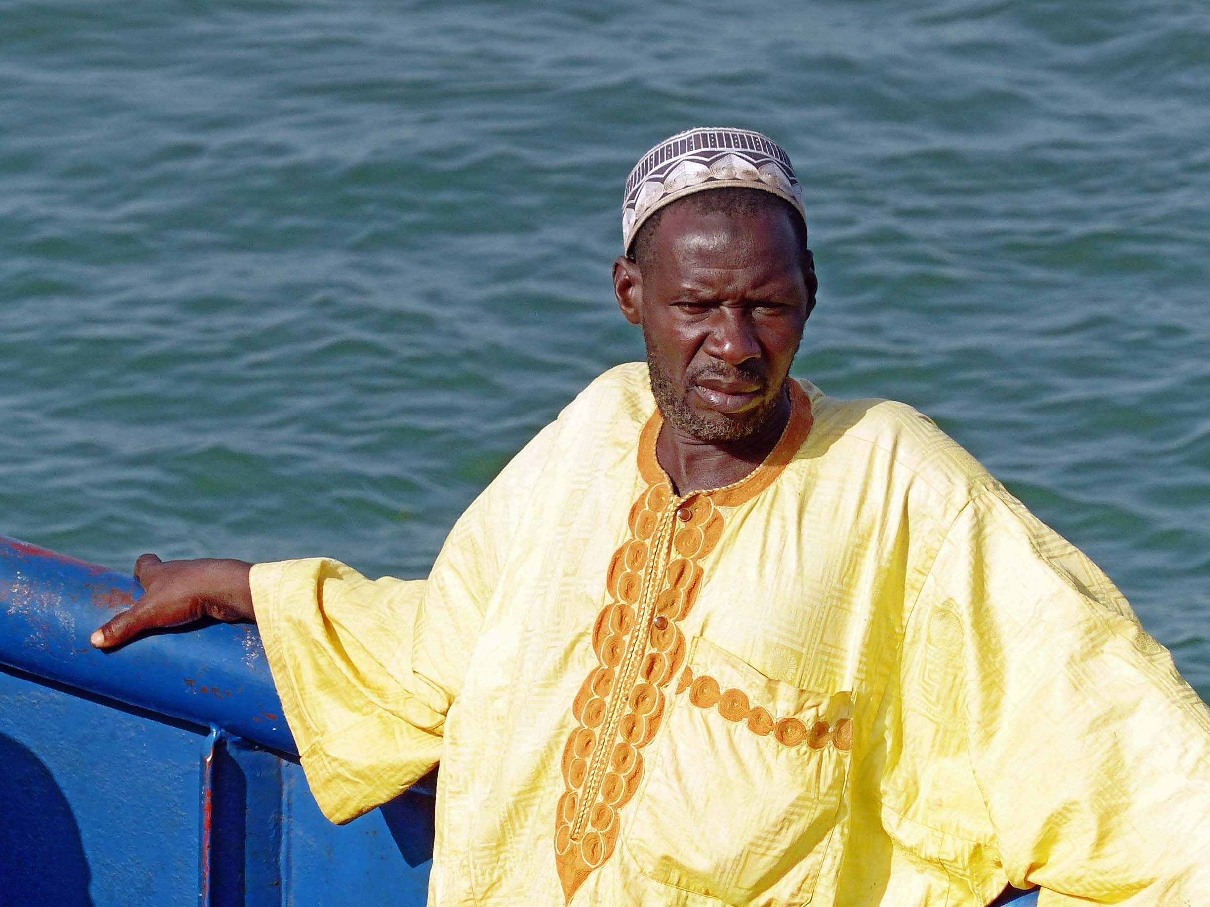 Man in African dress on a boat