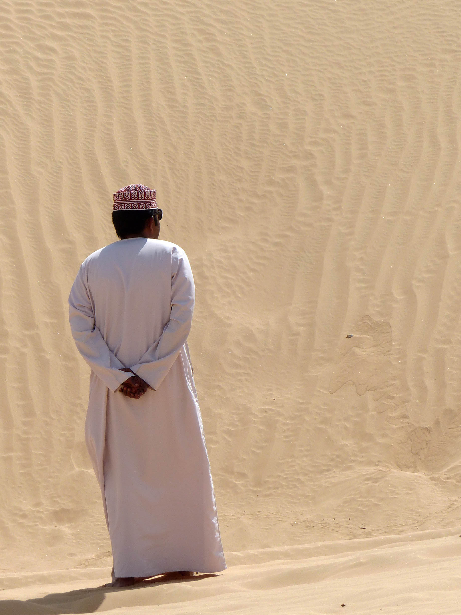Man in white robes on a sand dune