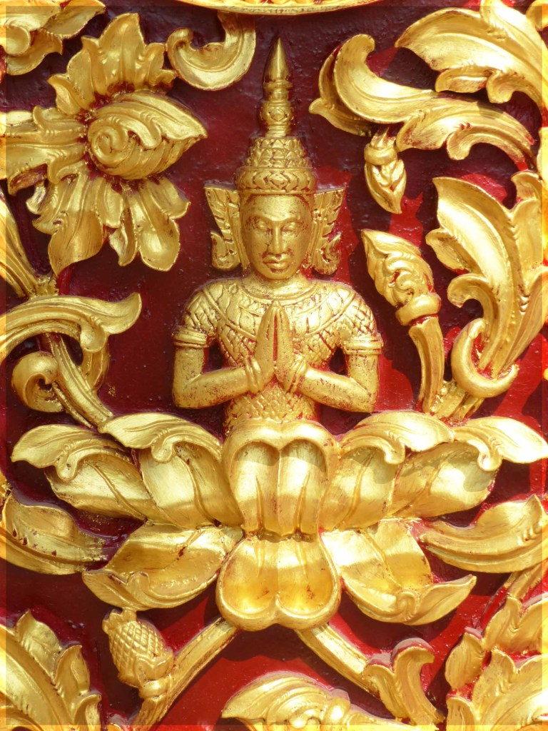 Small figure carved in gold on a red background