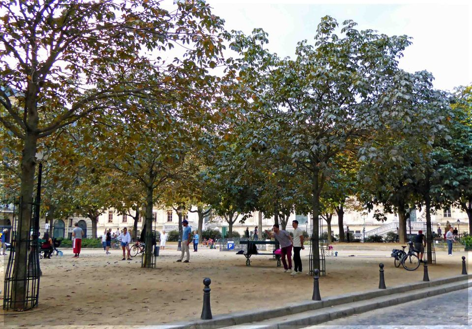 Square with trees and people playing boules