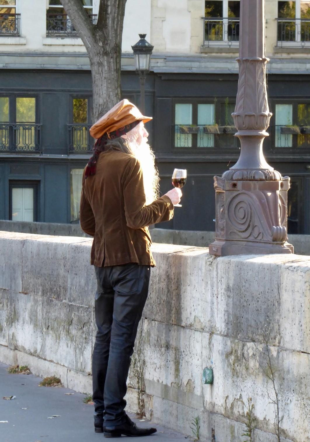 Man with a beard drinking wine on a bridge