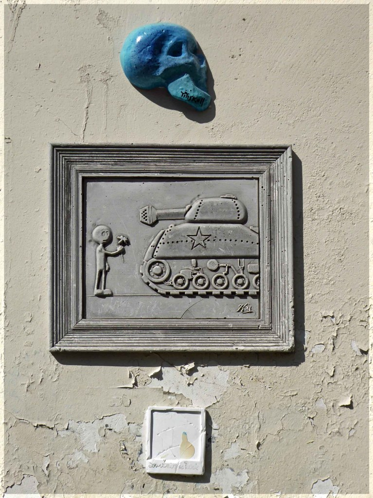 Small blue skull and image of tank with figure holding flowers