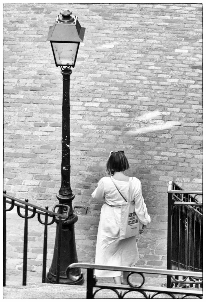 Black and white photo of lady walking down steps