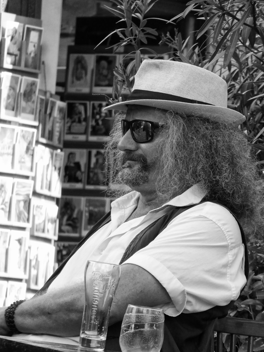 Black and white photo of a man with a hat in a cafe