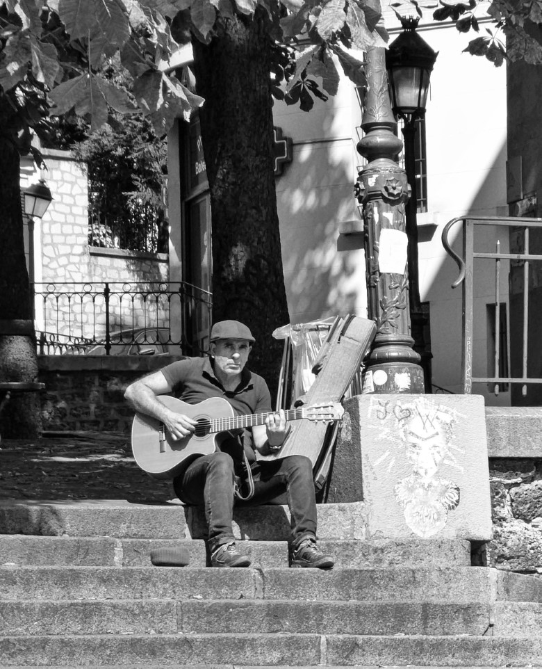 Black and white photo of a man playing a guitar on stone steps