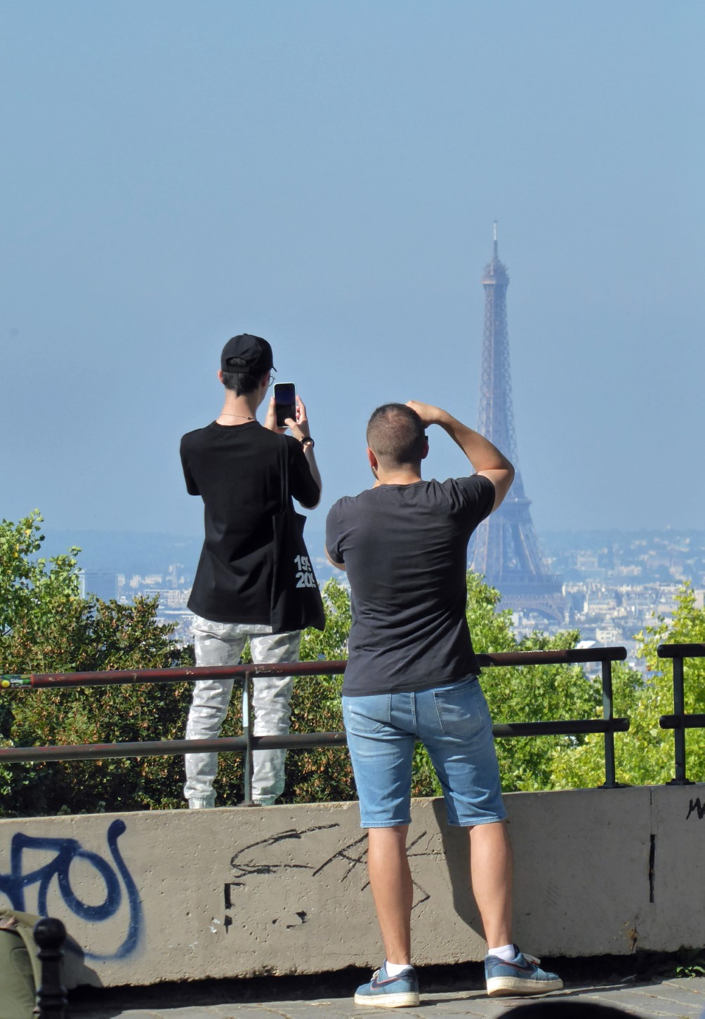 Two men taking photos of the Eiffel Tower, seen from behind